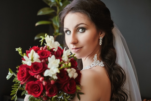 花の花束のクローズアップと花嫁の肖像画。花の美しい花束を持つ美しいブルネットの女性
