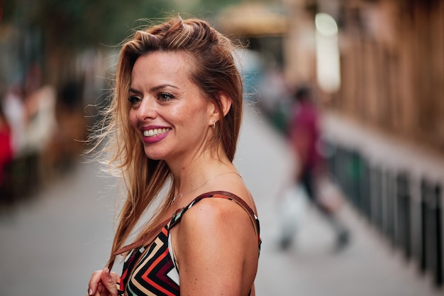 바르셀로나 시내에서 사진 촬영을 위해 포즈를 취한 모자를 쓴 갈색 머리 소녀의 초상화.