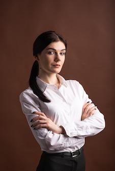 갈색 배경에 스튜디오에서 그녀의 팔을 교차 한 갈색 머리 비즈니스 여자의 초상화
