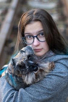 灰色のコートを着たブルネットの少女の肖像画は、彼女の腕にミニチュアシュナウザーを保持しています。ミニチュアシュナウザーと女の子があなたを見ています。好きなペットのコンセプト