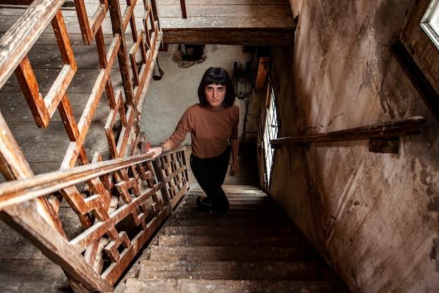 Портрет брюнетки на лестнице заброшенного дома, изображение при слабом освещении
