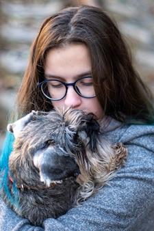 眼鏡をかけたブルネットの少女の肖像画は、子犬、犬、ミニチュアシュナウザーを腕に抱えています。好きなペットのコンセプト。