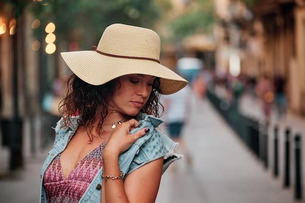 모자와 가방을 들고 바르셀로나 시 거리에서 사진 촬영을 위해 포즈를 취한 갈색 머리 소녀의 초상화.