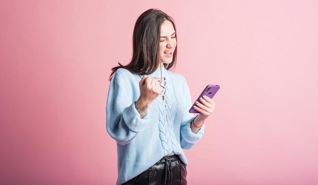 スマートフォンを使用し、勝者のジェスチャーを示すピンクの背景にブルネットの肖像画