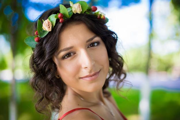 Портрет брюнетки с цветами в волосах в зеленом парке.