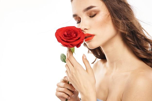 彼女の唇に赤い口紅とブルネット、ローズとグラスで美しい女性の肖像画