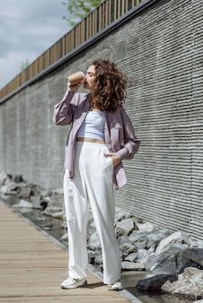 街の通りの背景にカップからコーヒーを飲むブルネットの女性の肖像画