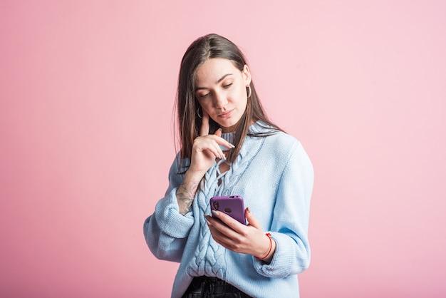 스마트 폰을 사용하는 분홍색 배경에 갈색 머리 여자의 초상화