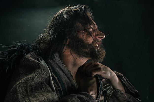 Портрет жестокого лысого викинга в боевой броне позирует на черном фоне. раннесредневековый период.