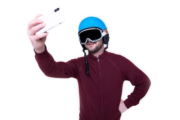 Портрет жестокого мужчины в лыжном шлеме и очках, который делает селфи