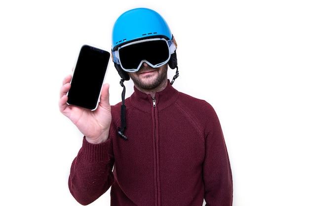Портрет брутального мужчины в лыжном шлеме и очках с мобильным телефоном