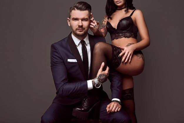 Портрет брутального мужчины в элегантном костюме трогает сексуальную девушку с татуировкой в нижнем белье на сером фоне