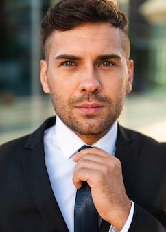 彼のネクタイを配置するビジネスマンの肖像画
