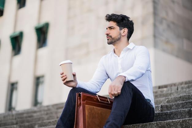 屋外の階段に座って仕事の休憩時間にコーヒーを飲むビジネスマンの肖像画。ビジネスコンセプト。