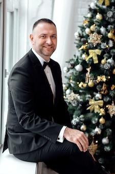 Портрет делового человека в черном костюме на камеру, сидя на окне возле елки.