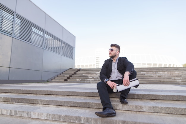 Портрет деловой человек, сидя на улице с кофе и документами в руках