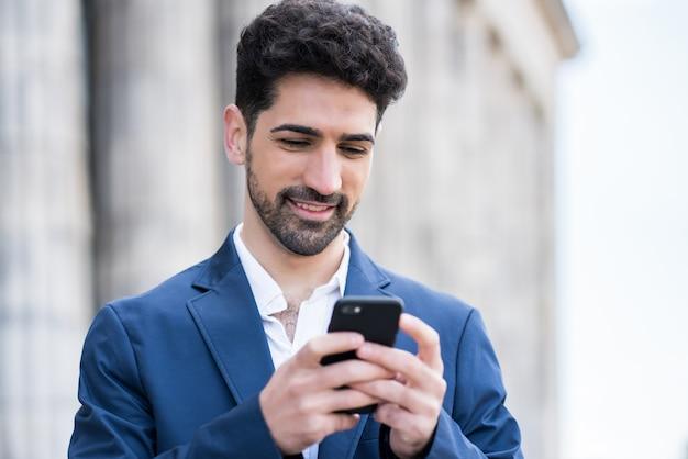 야외 거리에 서있는 동안 자신의 휴대 전화를 사용 하여 비즈니스 남자의 초상화. 비즈니스와 도시 개념.