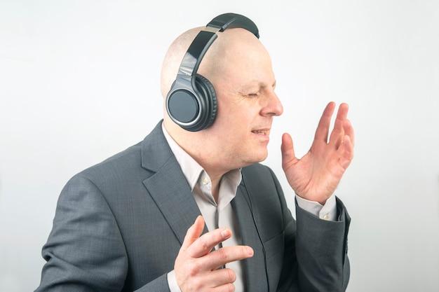 그의 좋아하는 음악을 듣고 휴식에 헤드폰으로 비즈니스 남자의 초상화