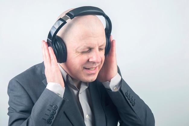 彼のお気に入りの音楽を聴いてリラックスしてヘッドフォンでビジネスマンの肖像画