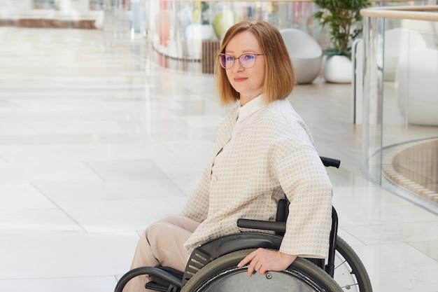 Портрет деловой женщины в инвалидной коляске в современном торговом центре.