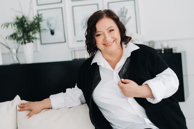Портрет деловой женщины в белой рубашке с жилетом, сидящей на диване в интерьере.