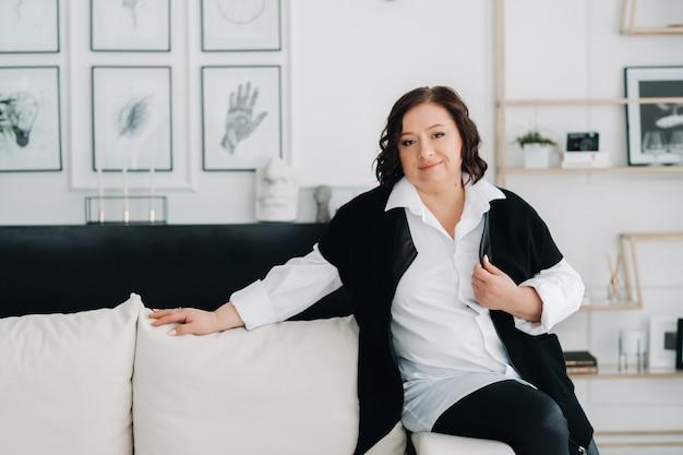 Портрет деловой женщины в белой рубашке с жилетом, сидящей на диване в интерьере