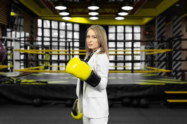 Портрет деловой женщины в желтых боксерских перчатках на фоне боксерского ринга