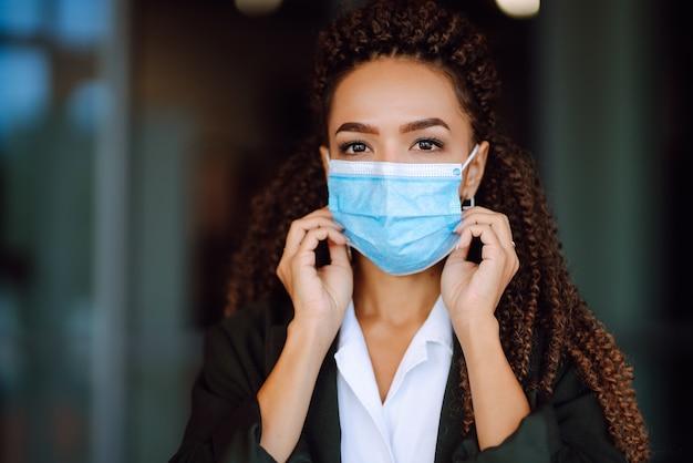 保護マスクを着用し、カメラで見ているビジネス女性の肖像画。