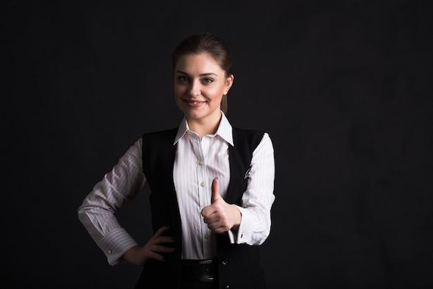 검은 배경에 스튜디오에서 좋은 제스처 엄지 손가락을 보여주는 비즈니스 여자의 초상화
