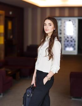 Портрет деловой женщины с портфелем в офисе.