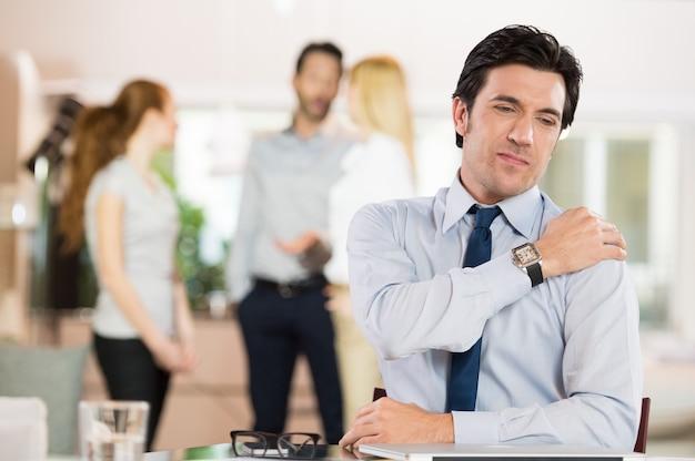 Портрет бизнесмена на работе страдает от боли в плече.