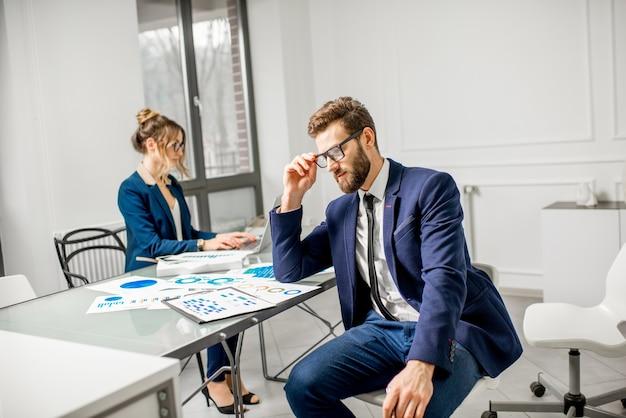 白いオフィスのインテリアで背景に女性アシスタントとドキュメントに取り組んでいるスーツに身を包んだビジネスマンの肖像画