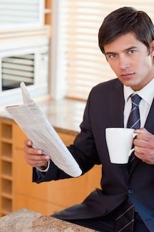 Портрет бизнесмена, пить чай во время чтения газеты
