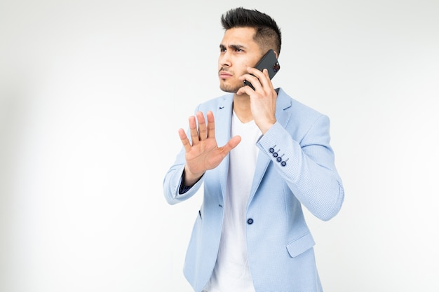 白い背景の上のパートナーと真剣に話している青いジャケットを着たビジネスマンの肖像画。
