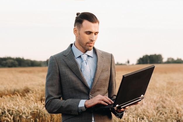 風車と夕方の空を背景に小麦畑でラップトップを保持しているスーツを着たビジネスマンの肖像画。