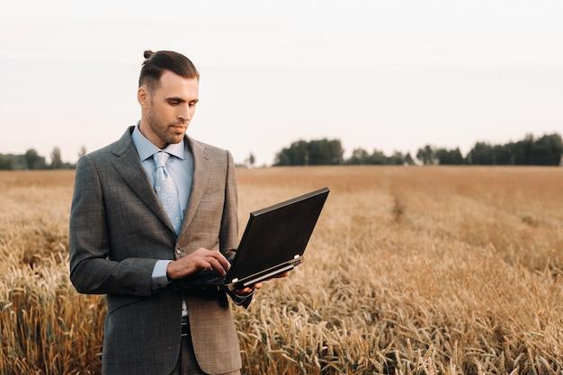 小麦畑でラップトップを保持しているスーツを着たビジネスマンの肖像画