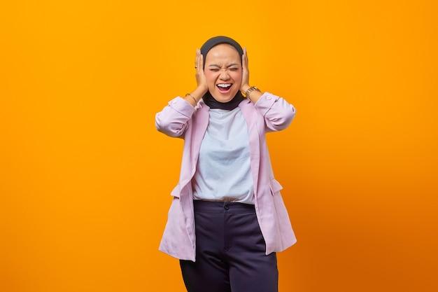 黄色の背景で隔離の彼女の耳を覆って笑っている実業家の肖像画