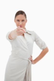Portrait of a businesswoman pointing at the viewer against a white background