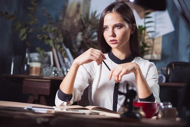 オフィスで働いていて、ノートブックで彼女の今後の会議の詳細をチェックし、ロフトスタジオで働いている実業家の肖像画