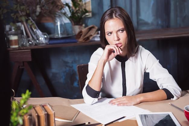 オフィスで働いていて、ノートブックで彼女の今後の会議の詳細をチェックし、ロフトで働いている実業家の肖像画。