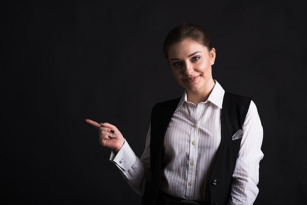 검정색 배경에 스튜디오에서 copyspace쪽으로 그녀의 손가락을 가리키는 사업가의 초상화
