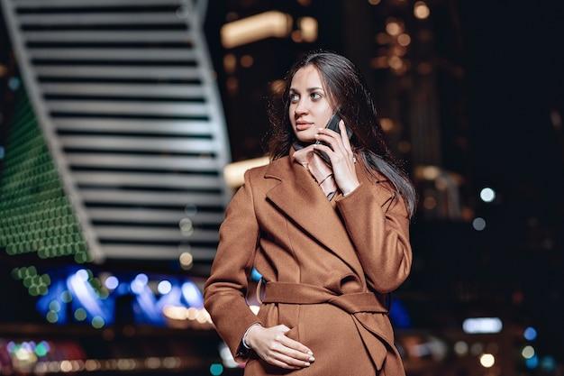 コートを着て、モスクワの夜の明かりを背景に電話で話している忙しいビジネス女性の肖像画。ロシアの