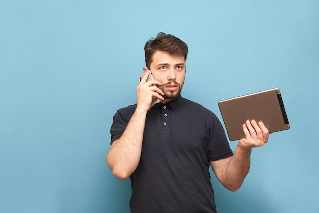 彼の手でタブレットで青の上に立って、電話で話している忙しい人の肖像画