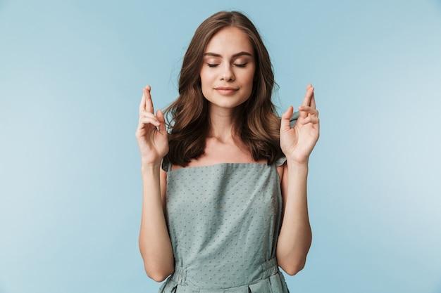 Портрет спокойной молодой женщины в платье, держащей пальцы