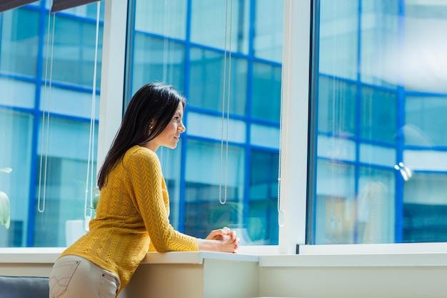 Портрет случайной деловой женщины, смотрящей в окно в офисе