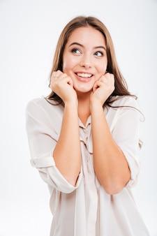 白い壁に何かについて考えているカジュアルな幸せな不思議な女性の肖像画