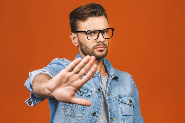 Портрет случайного человека, показывающего знак остановки, изолированный на оранжевом фоне.