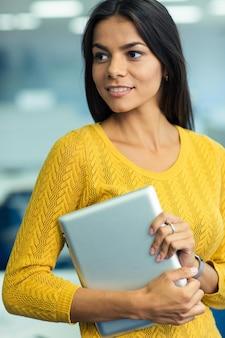 Портрет случайной симпатичной бизнес-леди, держащей планшетный компьютер в офисе и смотрящей в сторону