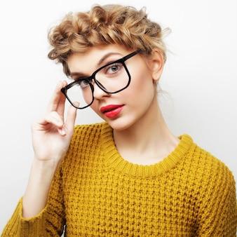 흰색 배경에 격리된 카메라를 바라보는 안경을 쓴 캐주얼한 여성의 초상화