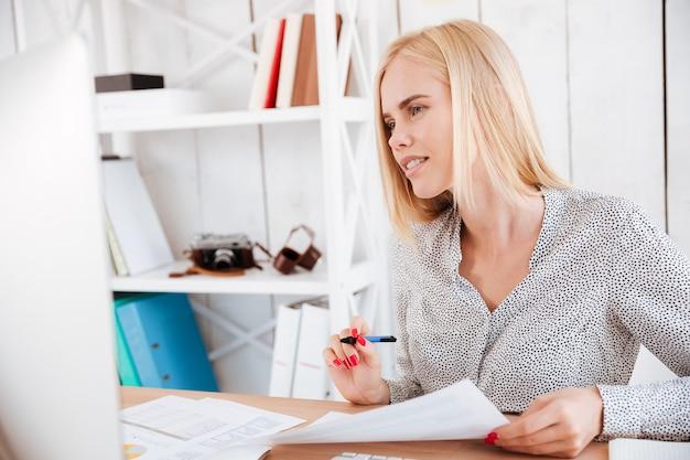 Портрет случайной молодой бизнес-леди, делая заметки, глядя на монитор компьютера